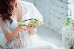 Fresh green wreath. Young female hands holding green rustic wreath close up. Royalty Free Stock Image