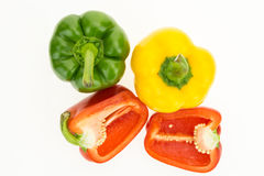 Fresh green, yellow and cut in two red bell peppers Stock Image