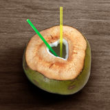 Fresh green young coconut with cut out heart shape and straws on wooden background Royalty Free Stock Photography