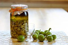 Fresh green,young walnuts and bottle of homemade liqueur taken as remedy for stomach aches Stock Photography