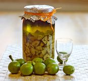 Fresh green,young walnuts and bottle of homemade liqueur taken as remedy for stomach aches Royalty Free Stock Photos