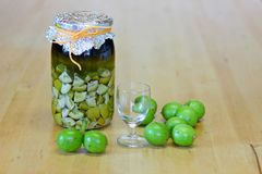 Fresh green,young walnuts and bottle of homemade liqueur taken as remedy for stomach aches Royalty Free Stock Images