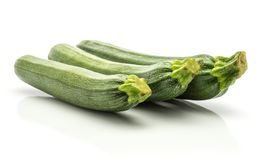 Fresh Green Zucchini  on white. Three green zucchini long raw courgettes in row  on white background Stock Image