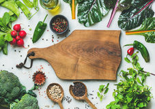 Fresh greens, raw vegetables and grains, wooden board in center. Fresh raw greens, unprocessed vegetables and grains over grey marble kitchen countertop, wooden Stock Photos