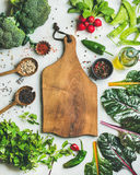 Fresh greens, raw vegetables and grains, wooden board in center. Fresh raw greens, unprocessed vegetables and grains over light grey marble kitchen countertop Royalty Free Stock Photography