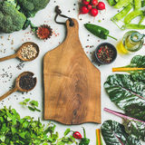 Fresh greens, vegetables and grains with wooden board in center. Fresh raw greens, unprocessed vegetables and grains over light grey marble kitchen countertop Royalty Free Stock Photography