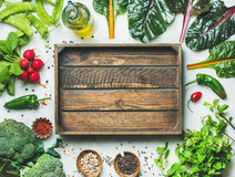 Fresh greens, vegetables and grains with wooden box in center. Fresh raw greens, unprocessed vegetables and grains over light grey marble kitchen countertop Royalty Free Stock Images