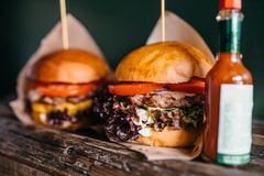 Fresh grilled burgers and ketchup on the table Royalty Free Stock Images