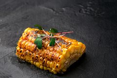 Fresh grilled corn cob on a dark stone background, copy space, top view. Still life. Flat lay Royalty Free Stock Photography