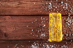 Fresh grilled corn cob with salt on wooden table. Copy space, top view Royalty Free Stock Photo