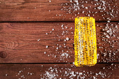 Fresh grilled corn cob with salt on wooden table. Copy space, top view Stock Photos