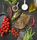 Fresh grilled meat. Grilled beef steak medium rare on wooden cutting board. Top view.. royalty free stock images