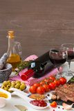 Fresh grilled meat. Grilled beef entrecote medium roast on black stone board, spice, olives oil, red wine and two full wine glasse Stock Image