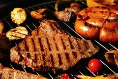 Fresh grilled meat steaks and vegetables on barbecue grate. Closeup stock photography