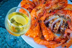 Fresh grilled shrimps, octopus on the dish and glass of white wine stock photography