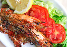 Fresh grilled shrimps with tomatoes, green salad and lemon Royalty Free Stock Photos
