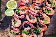 Fresh grilled skewers of seafood with lemon and parsley Royalty Free Stock Images
