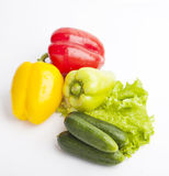 Fresh groceries on white background. Isolated,  with drops of water, green, yellow, red, Lettuce, cucumbers and paprika Royalty Free Stock Photos
