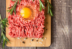 Fresh ground beef meat with egg and seasonings. On rustic wooden background. Top view Stock Photography