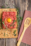 Fresh ground beef meat with egg and seasonings. On rustic wooden background. Top view Stock Photos
