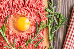 Fresh ground beef meat with egg and seasonings. On rustic wooden background. Top view Royalty Free Stock Photos
