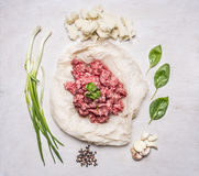 Fresh ground beef on a paper, with oregano, chives and pepper and garlic wooden rustic background top view Stock Image