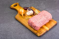 Fresh ground meat on wooden board with spices, vegetables. Studio Photo Royalty Free Stock Photography