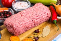 Fresh ground meat on wooden board with spices, vegetables. Studio Photo Royalty Free Stock Images