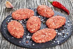 Fresh ground raw meat cutlets on slate plate Stock Photography