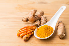 Fresh and grounded turmeric roots on wooden surface Royalty Free Stock Image