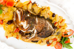 Fresh grouper with potatoes and tomatoes. Royalty Free Stock Images