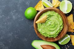 Fresh guacamole dip with avocado, lime and nachos on black table top view. Copy space.Traditional mexican food. royalty free stock photos