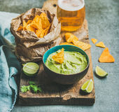 Fresh guacamole sauce in blue ceramic bowl, corn chips, beer Royalty Free Stock Photos