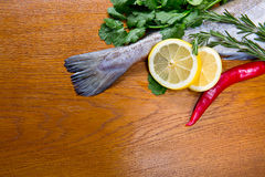 Fresh haddock, lemon, thyme and cilantro on the wooden bac Stock Photography