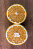 Fresh half cut oranges on wooden. Table Royalty Free Stock Image