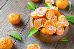 Fresh half mandarins in wooden bowl with leafs Stock Photo