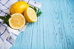 Fresh half and whole lemons on blue rustic boards. Royalty Free Stock Image