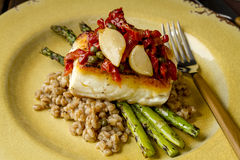 Fresh halibut filet on bed of farro royalty free stock photography