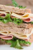 Fresh ham and cheese on white sandwich in rustic kitchen setting Stock Image