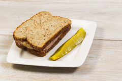 Fresh Ham Sandwich with Sliced Pickle on White Plate Stock Photo