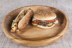 Fresh hamburger with a chop of marbled beef and fresh vegetables and hot dogs on a wooden tray Royalty Free Stock Photo