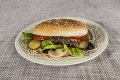 Fresh hamburger with a chop of marbled beef and fresh vegetables on a plate Stock Photography