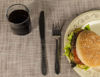 Fresh hamburger with a chop of marbled beef and fresh vegetables on a plate with a fork and knife Royalty Free Stock Photos