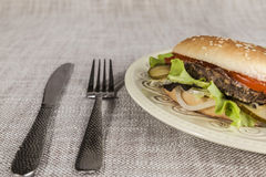 Fresh hamburger with a chop of marbled beef and fresh vegetables on a plate with a fork and knife Stock Image