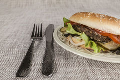 Fresh hamburger with a chop of marbled beef and fresh vegetables on a plate with a fork and knife Stock Images
