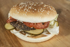 Fresh hamburger with a chop of marbled beef and fresh vegetables on a wooden background Stock Photo