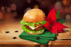 Fresh hamburger and christmas decor with poinsettia flower.  Stock Image