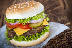 Fresh hamburger. Classic hamburger with cheese and vegetables on the baking paper and wooden tabletop Stock Image