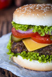 Fresh hamburger. Classic hamburger with cheese and vegetables on the baking paper and wooden tabletop Stock Images