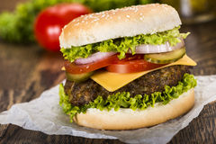 Fresh hamburger. Classic hamburger with cheese and vegetables with defocused vegetables behind, photographed on the baking paper and wooden tabletop Royalty Free Stock Image